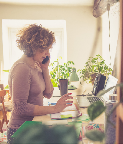 woman on phone looking at laptop and planner